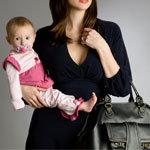 üzletiesen felöltözött anyuka kezében tartja a gyermekét