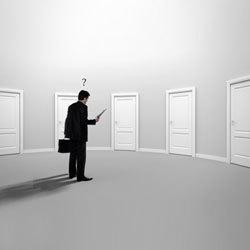 ajtók előtt álló öltönyös férfi